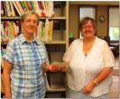 Grenville WI member Joyce Crooks presents dontation to librarian Celine Joly